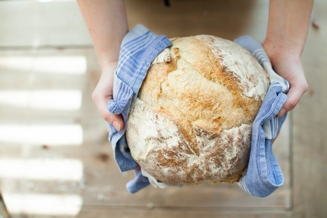 Person holding fresh baked bread wrapped in a towel